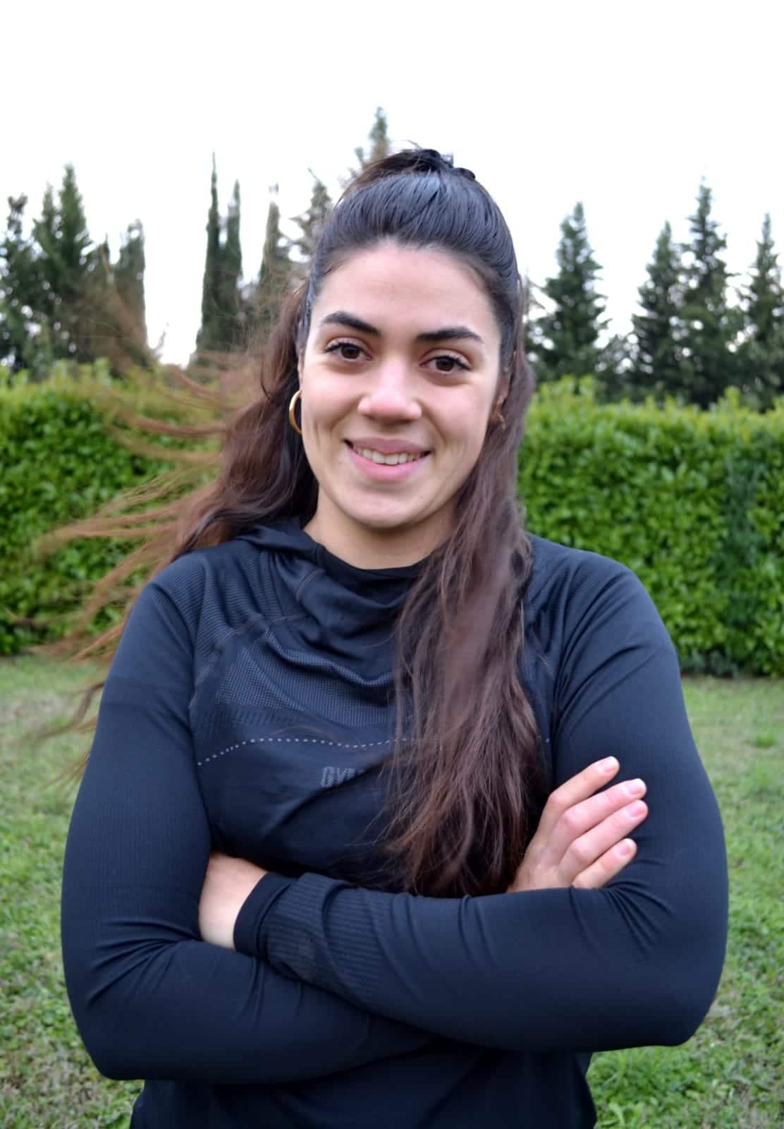 Marika, coach sportive, les bras croisés et souriante, en tenue de sport.